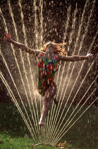 Girl running through sprinkler