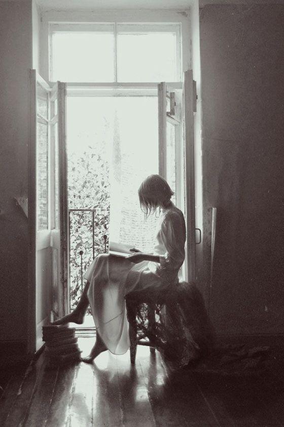 reading in window girl