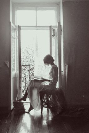 reading in window girl