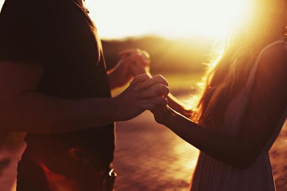 couple holding hands in sunshine