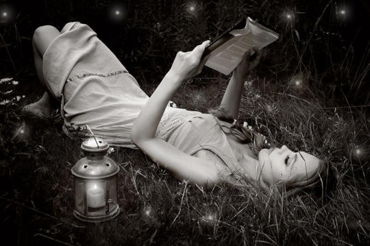 woman reading with fireflies